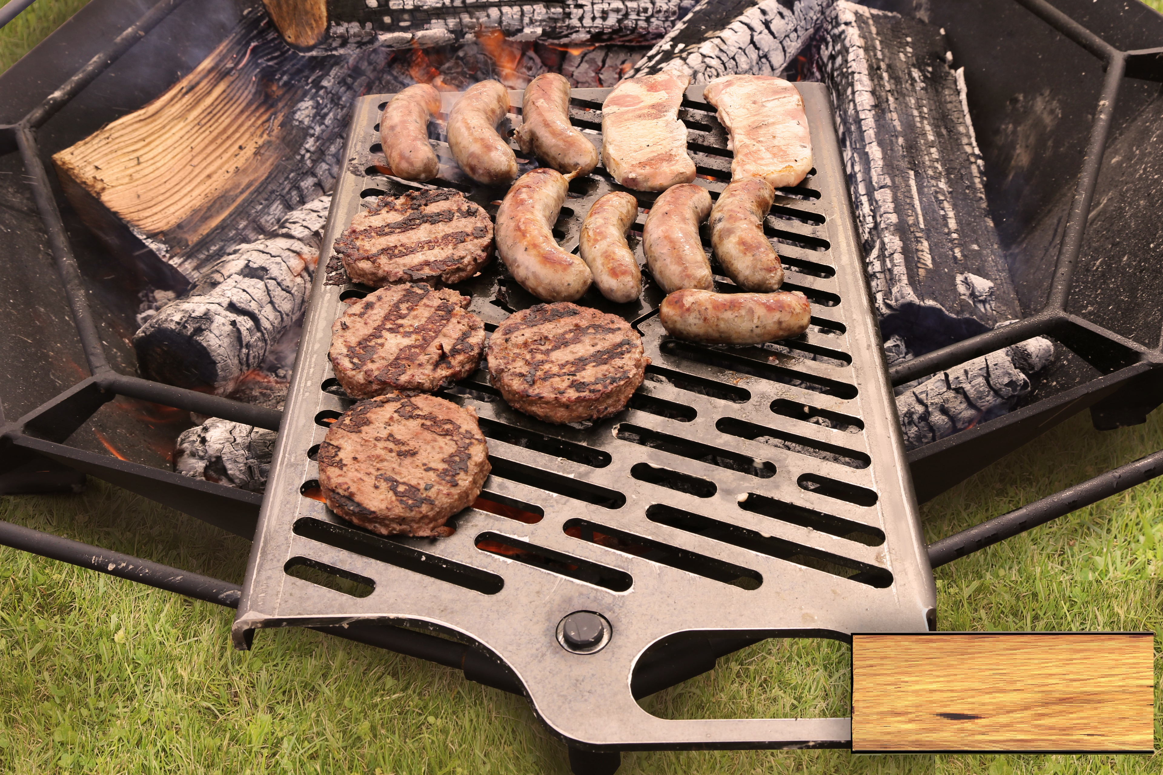 Burgers and sausages cooking on a grill over a fire pit